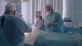 Защитная одежда медсестры нося помогая во время хирургии сток-видео