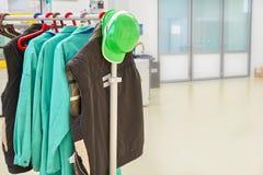 Защитные одежды и зеленый шлем безопасности на пальто кладут на полку на фабрике Стоковые Изображения