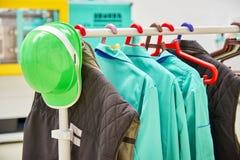 Защитные одежды и зеленый шлем безопасности на пальто кладут на полку Стоковые Изображения