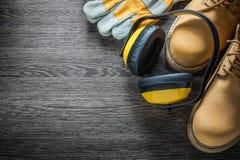 Защитные перчатки работая earmuffs ботинок на деревянной доске Стоковые Изображения