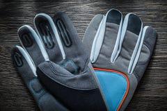 Защитные работая перчатки на винтажной деревянной доске Стоковое Фото