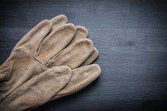 2 защитных перчатки на темной деревянной доске Стоковые Изображения