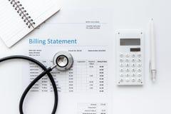 Заявление выписывания счетов здравоохранения с стетоскопом ` s доктора на белом модель-макете взгляд сверху предпосылки стоковое фото