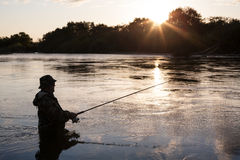 Задвижки рыболова семг на заходе солнца Стоковые Фотографии RF