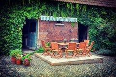 Задворк фермы с таблицей и стульями стоковые фото