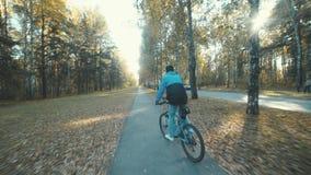 Задействовать в парке осени Молодой человек в крышке ехать велосипед акции видеоматериалы