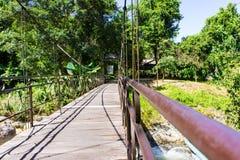 Залив водопада Yang, Вьетнам прикрепленный на петлях пешеходный мост над рекой запас Стоковые Фото