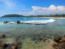 Залив Mirissa с утесами, зелеными цветами и океанскими волнами стоковое фото rf