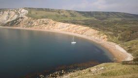 Залив Worbarrow к востоку от бухты Lulworth и около Tyneham на побережье Англии Великобритании Дорсета с яхтой видеоматериал