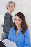 Задирать на работе: более старая бизнес-леди ревнива стоковое фото rf