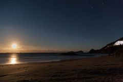Залитый лунным светом пляж с звездами в ночном небе Стоковые Изображения RF