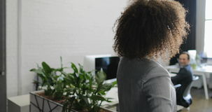 Заднее вид сзади Афро-американской бизнес-леди приходя к современному офису держа велосипед акции видеоматериалы