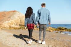 Заднее изображение взгляда африканских любящих пар идя outdoors Стоковые Фото