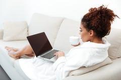 Заднее изображение взгляда молодой африканской женщины используя портативный компьютер Стоковое Изображение RF