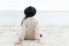 Заднее фото взгляда кавказской дамы сидя outdoors на пляже Стоковые Изображения RF