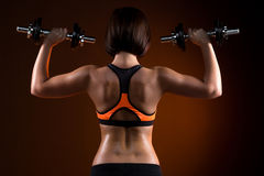 Задние молодые девушки фитнеса с гантелями Стоковые Изображения RF