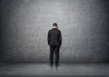 Задний бизнесмен взгляда при обхватыванная голова стоя перед бетонной стеной Стоковое фото RF