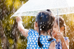 Задний взгляд 2 азиатских маленьких девочек с зонтиком Стоковое Изображение RF