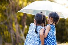 Задний взгляд 2 азиатских маленьких девочек с зонтиком Стоковые Фотографии RF