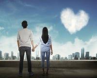 Задний взгляд азиатских пар держа руку смотря небо Стоковое Изображение RF