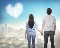 Задний взгляд азиатских пар держа руку смотря небо Стоковая Фотография RF