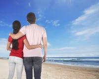 Задний взгляд азиатских пар держа руку смотря небо Стоковое Фото