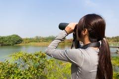 Задний взгляд азиатского использования молодой женщины бинокулярного стоковое фото