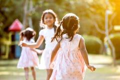 Задний взгляд азиатской девушки ребенка бежать к ее другу Стоковое Изображение
