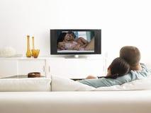 Задний взгляд ласковых пар на софе смотря телевидение стоковые изображения rf