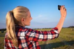 Задний взгляд белокурой женщины делая фото selfie на smartphone в m Стоковые Фотографии RF