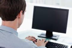 Задний взгляд бизнесмена работая с компьютером Стоковая Фотография RF