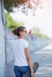 Задний взгляд девушки нося пустую белую футболку, джинсы представляя против грубой стены улицы Стоковые Изображения RF