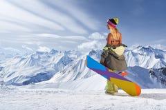 Задний взгляд девушки при красочный сноуборд смотря отсутствующие горы Стоковая Фотография RF