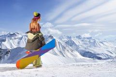 Задний взгляд девушки при красочный сноуборд смотря отсутствующие горы Стоковое Изображение