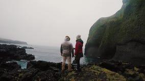 Задний взгляд детенышей путешествуя пары стоя на утесах около моря и наслаждаясь красивым видом совместно видеоматериал