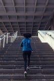 Задний взгляд женщины бежать вверх лестницы Стоковая Фотография RF