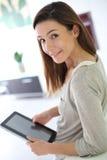 Задний взгляд женщины брюнет в кухне используя таблетку Стоковые Изображения
