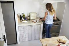 Задний взгляд женщины варя в кухне, читая книгу рецепта Стоковая Фотография RF
