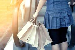 Задний взгляд женщины держа хозяйственные сумки на эскалаторе Стоковые Фотографии RF