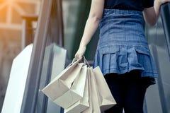 Задний взгляд женщины держа хозяйственные сумки на эскалаторе Стоковые Изображения RF