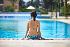Задний взгляд женщины ослабляя в бассейне Стоковое фото RF
