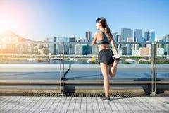 Задний взгляд женщины протягивая ноги в городе Стоковое Изображение