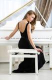 Задний взгляд женщины сидя и играя рояль стоковое изображение