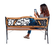 Задний взгляд женщины сидя на стенде и взглядах на экране таблетка Стоковая Фотография RF