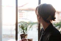 Задний взгляд женщины сидя на таблице в кафе Стоковое Фото