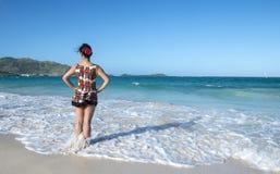 Задний взгляд женщины стоя в океане 1 стоковые изображения rf
