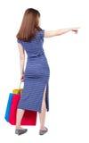 Задний взгляд женщины с указывать хозяйственных сумок Стоковые Изображения RF