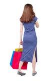 Задний взгляд женщины с хозяйственными сумками Стоковое фото RF
