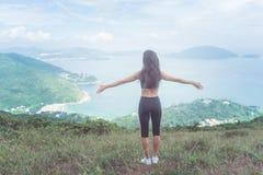 Задний взгляд женщины фитнеса стоя на зеленой горе при ее протягиванные оружия смотрящ на море выражать ландшафта Стоковые Изображения