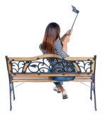 Задний взгляд женщины для того чтобы сделать портрет ручки selfie сидя на стенде Стоковое Фото
